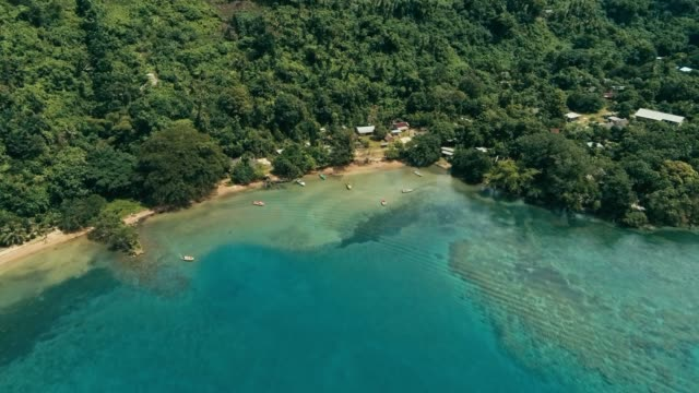 aerial drone image of a south pacific village on a remote island with a beautiful coral reef and lush tropical rainforest jungle while a small motor boat approaching aerial drone image of a south pacific village on a remote island with a beautiful coral reef and lush tropical rainforest jungle while a small motor boat approaching pacific islands stock videos & royalty-free footage