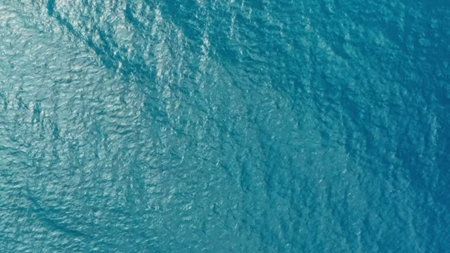 vídeos de stock e filmes b-roll de aerial drone image of the deep blue clear sea ocean water with small waves rolling - water
