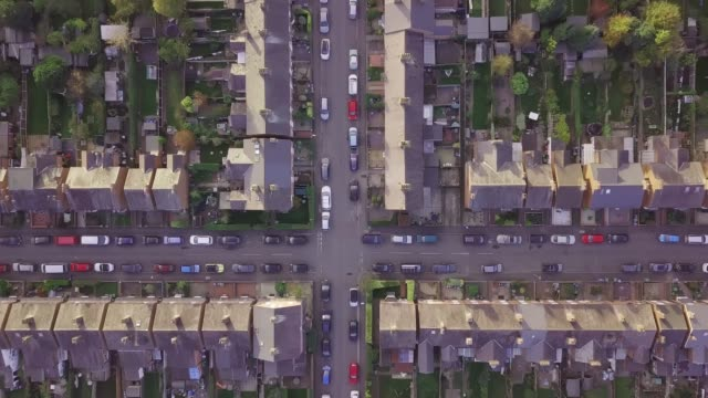 vídeos de stock e filmes b-roll de aerial drone lifestyle concept flying over a street lined with british terraced houses during the golden hour as the sun is setting. - suburbano