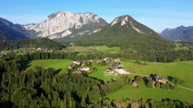 vídeos de stock, filmes e b-roll de filme aéreo de drone da vila, montanha e lago ao redor da vila hallstatt, alpes austríacos, alta áustria, europa - tyrol state austria