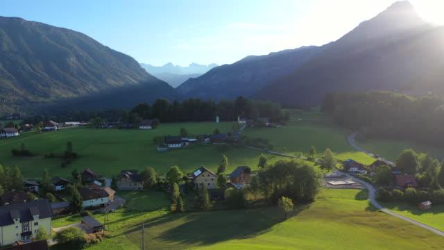 vídeos de stock, filmes e b-roll de filme aéreo drone da aldeia, montanha e lago ao redor de hallstatt village, alpes austríacos, alta áustria, europa - tyrol state austria