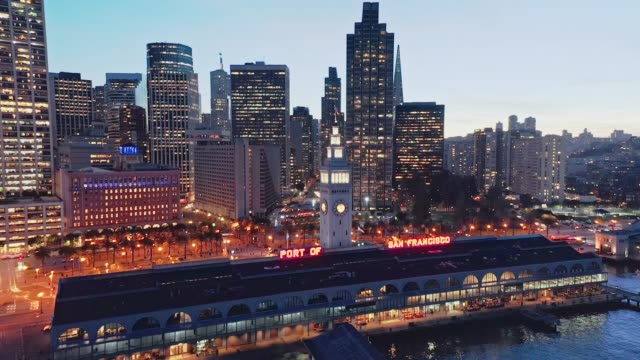 Aerial drone of the San Francisco city skyline and Ferry Building at night - crane down reveal shot