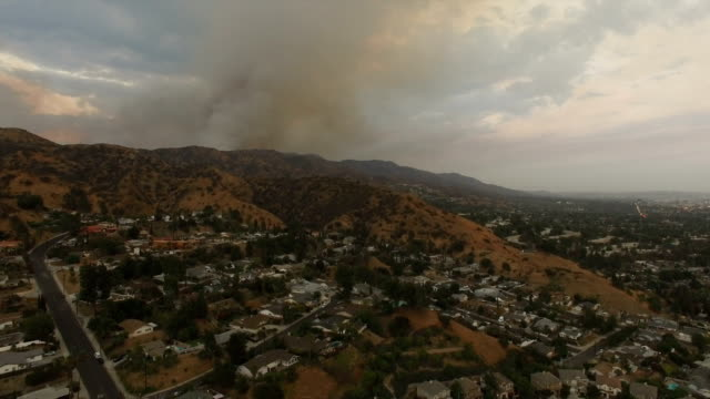 Aerial drone over neighborhood with smoke from wildfires video