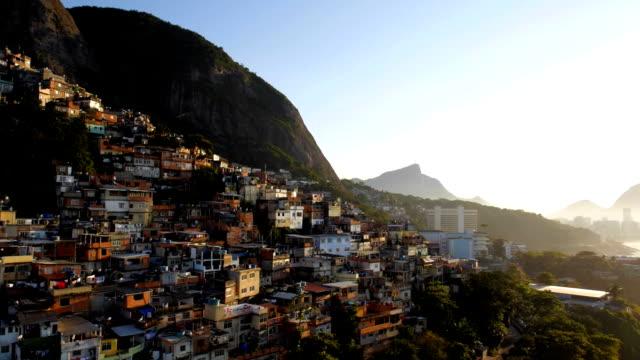 Aerial drone panning shot of hillside favela houses at sunrise