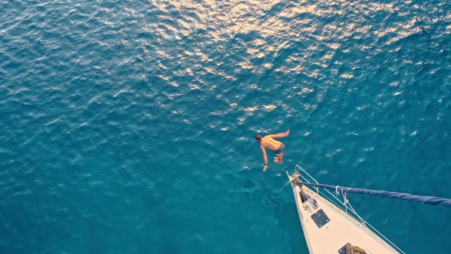 4K Aerial drone point of view man jumping off sailboat into sunny, blue ocean, real time