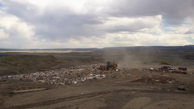 Aerial drone point of view of a commercial landfill garbage dump with tractors scraping the trash