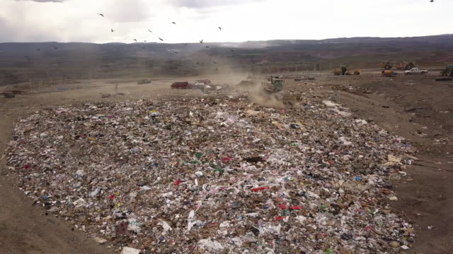 Aerial drone point of view of a commercial landfill garbage dump with tractors scraping the trash Aerial drone point of view of a commercial landfill garbage dump with tractors scraping the trash scavenging stock videos & royalty-free footage