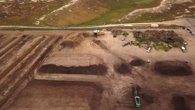 Aerial Drone Point of View of an Organic Mulching Composting Facility with Piles of Tree Branches and Organic Materials for Recycling