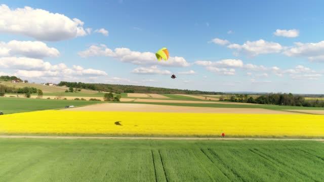 stockvideo's en b-roll-footage met luchtfoto drone oogpunt paraglider met parachute over landelijke landschap, real-time - er even tussenuit