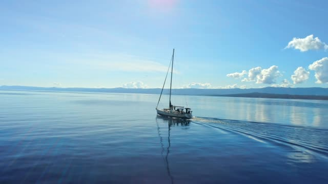 4k aerial drone point of view sailboat on tranquil sunny blue ocean, real time - хорватия стоковые видео и кадры b-roll