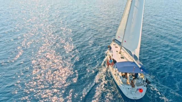 4k воздушный беспилотный точки зрения парусник на спокойный, солнечный синий океан, в режиме реального времени - яхта стоковые видео и кадры b-roll