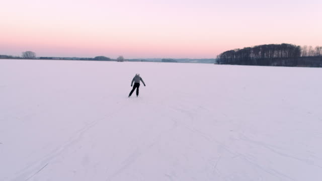 4k aerial drone point of view teenage boy ice skating on vast, tranquil frozen lake, real time - acqua ghiacciata video stock e b–roll