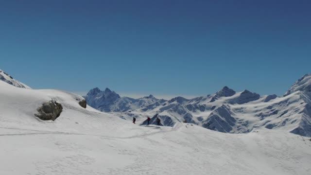 antenn drönare sköt kretsande en grupp skidåkare som står på kanten av ett berg som tittar på mount elbrus - vintersport bildbanksvideor och videomaterial från bakom kulisserna