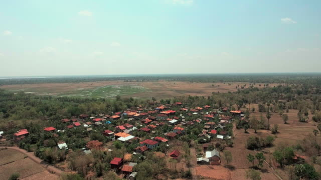 aerial drone shot : fly backwards revealing a sleeping village during the dry season. aerial drone shot : fly backwards revealing a sleeping village during the dry season. ( asia) back to back stock videos & royalty-free footage