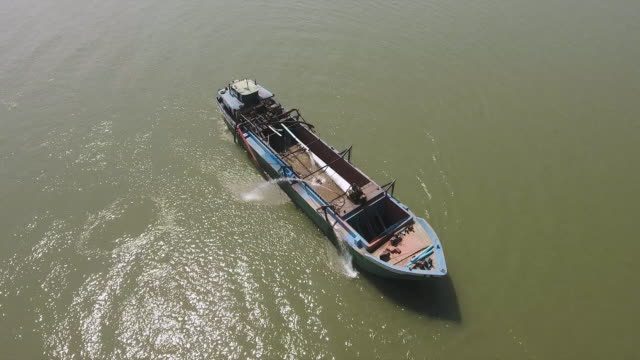 aerial drone shot : fly over a dredging boat on river pumping riverbed sand - chiatta video stock e b–roll