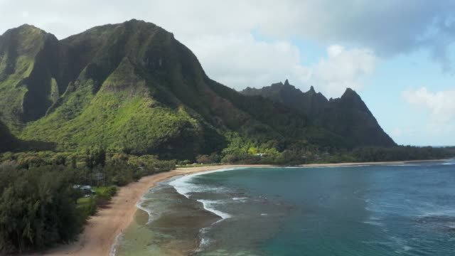 Aerial drone shot flying along the coast of Tunnels Beach on the north shore of Kauai in Hawaii - video