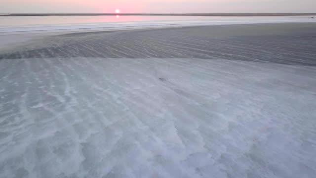 vídeos de stock e filmes b-roll de aerial drone shot flying over vast cracked salt flats in azov sea, ukraine at sunset, mineral deposits - parque nacional do vale da morte