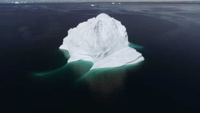 vídeos de stock e filmes b-roll de aerial drone shot flying towards a large iceberg in greenland in the arctic - iceberg