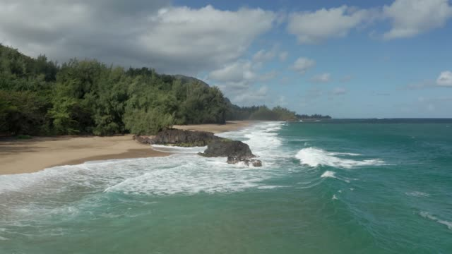 Aerial drone shot flying towards the rocky end of Lumahai Beach on the north shore of Kauai in Hawaii - video