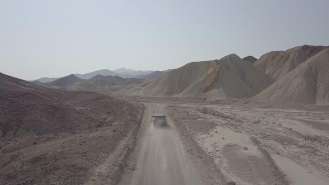 vídeos de stock e filmes b-roll de aerial drone shot following vehicle in desert death valley - parque nacional do vale da morte