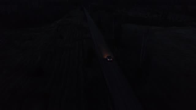 aerial drone shot of 4x4 driving in night - сельская дорога стоковые видео и кадры b-roll