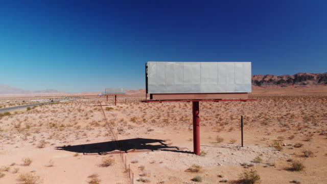 Aerial Drone Shot of a Blank, Abandoned Billboard Advertisement by the Side of Interstate 15 in the Utah Desert Under a Clear, Blue Sky