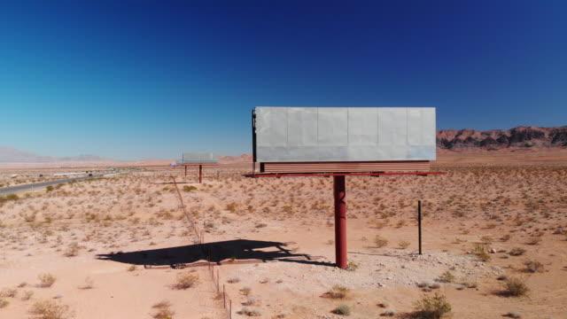 明確の下でユタ州の砂漠の道路の 15 の側で空白、放棄された看板広告の空中ドローン ショット青空します。 - 州間高速道路点の映像素材/bロール