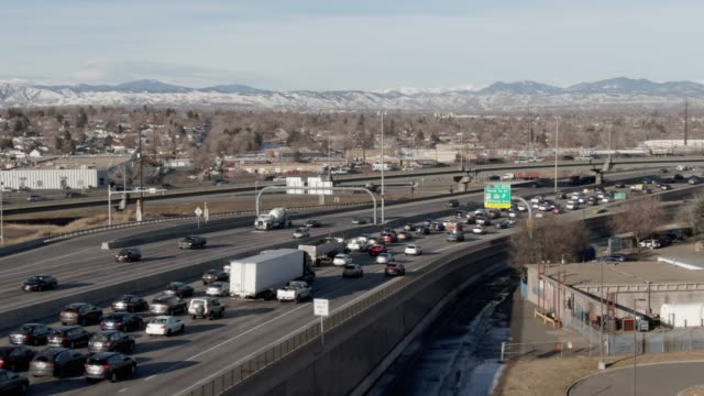 aerial drone shot of a busy interstate 70 overpass in denver on a sunny morning with the rocky mountains in the background - traffic filmów i materiałów b-roll