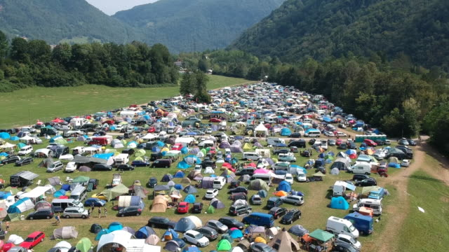 Aerial drone shot of a camping ground at a music festival in a green and lush mountainous area.