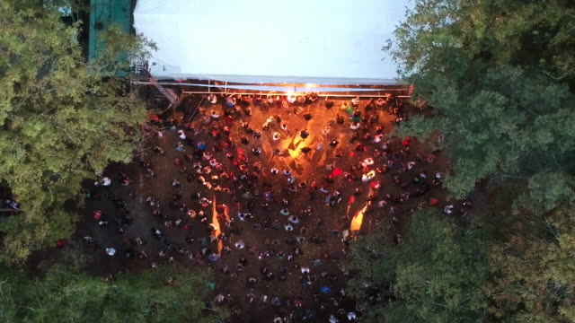 Aerial drone shot of a crowd watching an outdoor concert event at a festival with flashing lights in a forest.