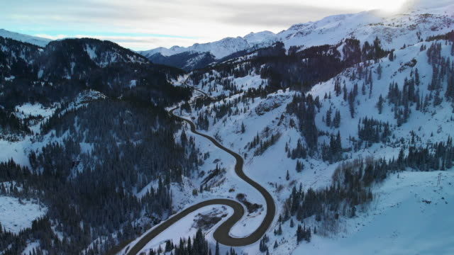 aerial drone shot of a curvy, snowy red mountain pass (road: million dollar highway) in the san juan mountains (rocky mountain range) outside of ouray, colorado in winter surrounded by a forest of trees - strada tortuosa video stock e b–roll