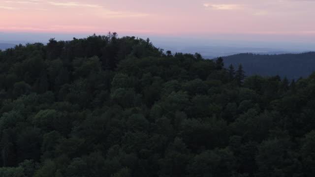 vidéos et rushes de tir aérien de drone d'une colline et d'une forêt boisées au coucher du soleil - évasion du réel