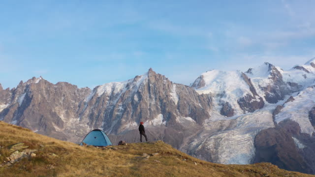 Aerial drone shot of a hiker standing outside a blue tent near Mont Blanc