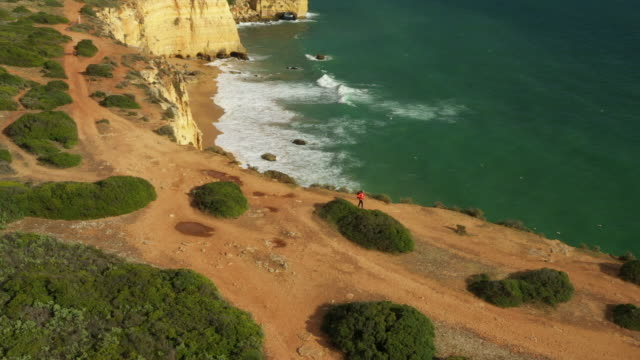 vídeos de stock e filmes b-roll de aerial drone shot of a jogger hiking along the ocean bluffs near lisbon - people lisbon