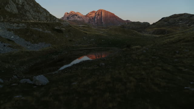 aerial drone shot of a lake and mountains in durmitor national park at sunset - эскапизм стоковые видео и кадры b-roll
