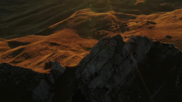 luftdrohne von einem mann, der bei sonnenuntergang auf einer gratlinie im durmitor-nationalpark wandert - eskapismus stock-videos und b-roll-filmmaterial