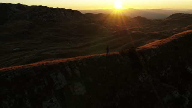 stockvideo's en b-roll-footage met lucht drone shot van een man wandelen langs een ridgeline in durmitor national park bij zonsondergang - minder dan 10 seconden