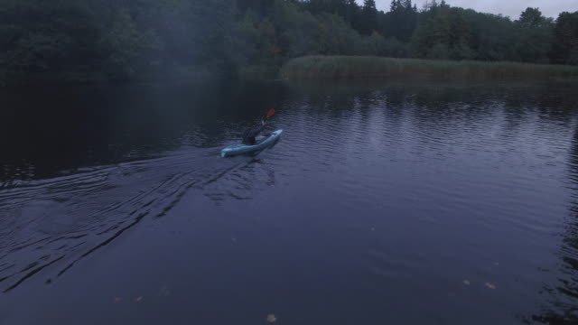Aerial drone shot of a man in a blue kayak in a river in the forest. video