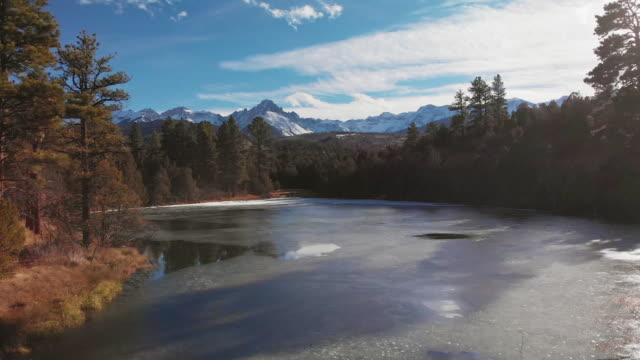aerial drone shot of a mountain lake landscape at the base of the san juan mountains (rocky mountains) outside of ouray, colorado under a blue, partially cloudy sky - скалистые горы стоковые видео и кадры b-roll