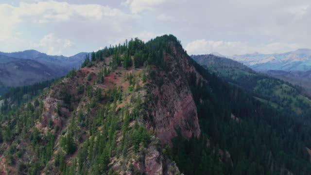 vidéos et rushes de drone aérien tiré d'un pic de montagne dans le parc national de grand teton dans le wyoming un jour partiellement nuageux - étendue sauvage scène non urbaine