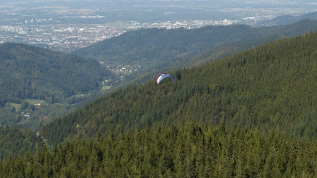 Aerial drone shot of a paraglider over a forest near Freiburg