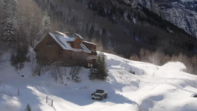 antenn drönare skott av en person snowblowing framför en pittoresk, snötäckta fjällstuga på en vinter dag - klippiga bergen bildbanksvideor och videomaterial från bakom kulisserna