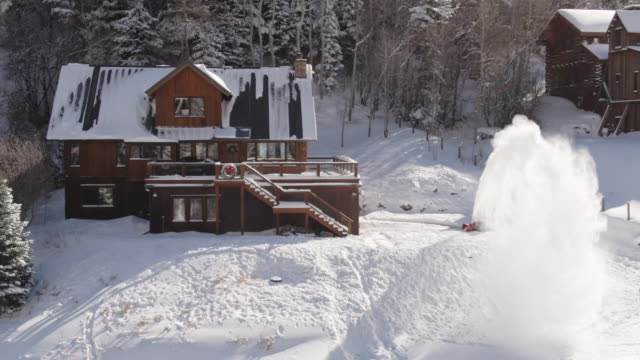 Aerial Drone Shot of a Person Snowblowing in Front of a Picturesque, Snow-Covered Mountain Cabin with Children Sledding Outside on a Bright Winter Day