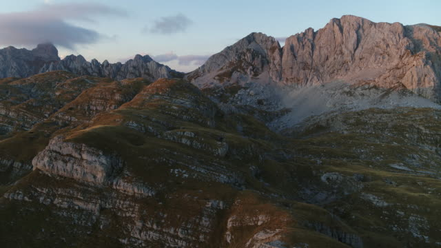 aerial drone shot of a rocky mountain range in durmitor national park at dusk - эскапизм стоковые видео и кадры b-roll