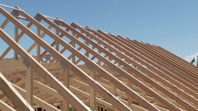 aerial drone shot of a row of wooden roof trusses of a framed house on a construction site on a sunny day - intelaiatura video stock e b–roll