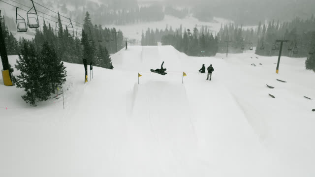 Aerial Drone Shot of a Snowboarder in Full Winter Gear Completing a