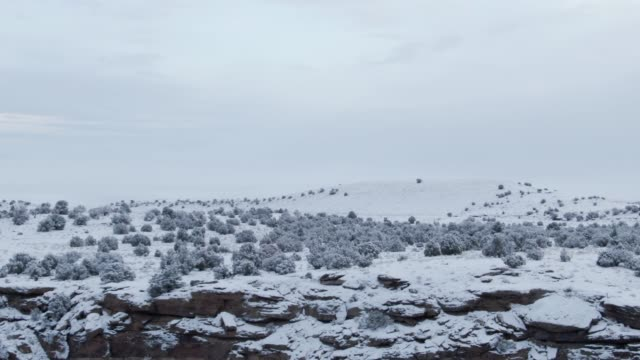 Aerial Drone Shot of a Snowy, Rocky Desert Landscape in Winter under an Overcast Sky