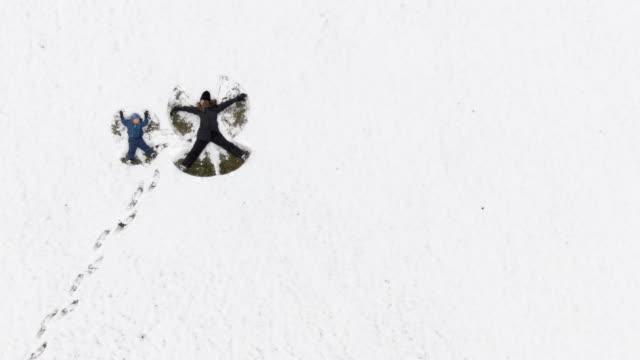 luftbild-drohne schuss von dreißig-etwas mutter und ihre drei jahre alten sohn machen schnee engel in ein großes schneebedecktes feld - 2 3 jahre stock-videos und b-roll-filmmaterial