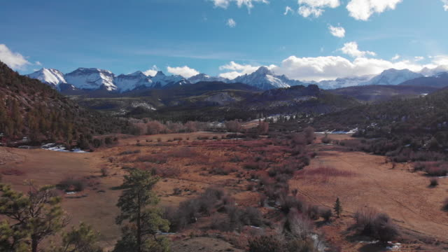 aerial drone shot of a valley landscape at the base of the san juan mountains (rocky mountains) outside of telluride, colorado under a blue, partially cloudy sky - колорадо стоковые видео и кадры b-roll