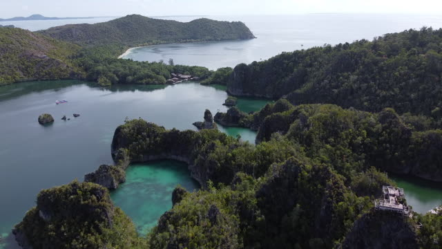 vídeos de stock e filmes b-roll de aerial drone shot of an archipelago and dwellings on the ocean - arquipélago